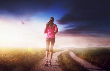 Woman running in fit wear in majestic landscape