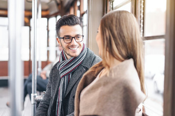 Young couple having a conversation while sitting inside vintage tram transport - Happy people talking during a journey in bus city center - Love, relationship and transportation concept