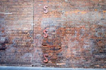 Old brick wall along a sidewalk with three S-shaped wall braces, horizontal
