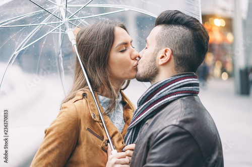 Young Couple Kissing Under Umbrella In Rainy Day In The City Center