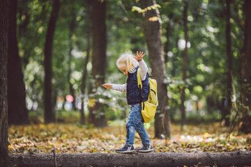 The theme children outdoor activities. Funny little baby Caucasian blond girl walks through forest overcoming obstacles, tree fell, log. Baby hiking big funny backpack in autumn forest park