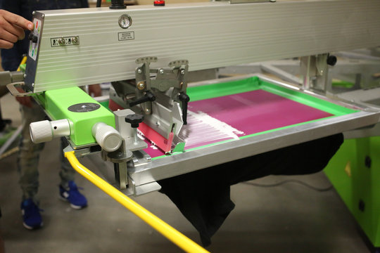 screen printer flooding a pink screen