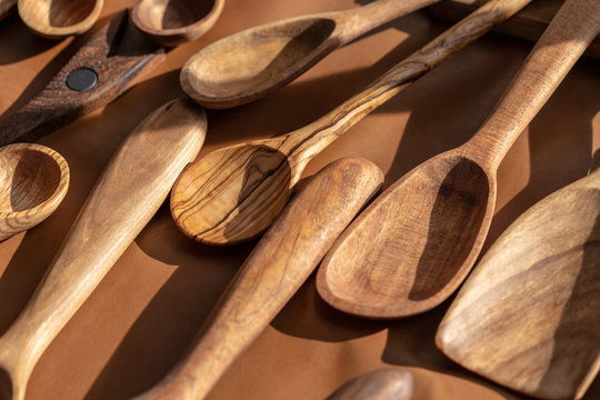 spoons made of many different wood types sitting on a table covered with brown leather outside in the sun