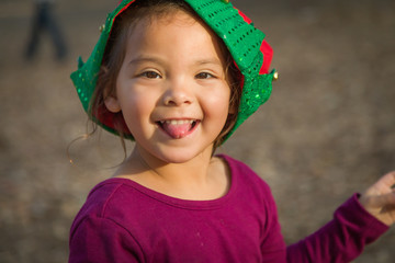 Cute Mixed Race Young Baby Girl Having Fun Wearing Christmas Hat Outdoors