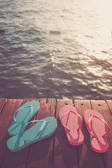 Flip flops at the wooden pier during sunset. Luxury vacation resort. Holiday getaway concept
