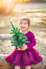Cute Mixed Race Young Baby Girl Having Fun With Christmas Tree Outdoors On Log