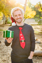 Handsome Festive Young Caucasian Man Holding Christmas Gift Outdoors