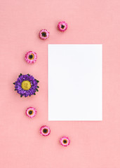 Flowers and white sheet of paper on pink canvas