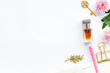Perfume on feminine desk. Women's accessories. Perfume near notebook for dairy among flowers on white background top view space for text