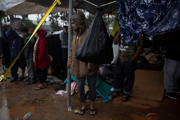 Migrants, part of a caravan of thousands from Central America trying to reach the United States, stand under a tent at a temporary shelter during heavy rainfall in Tijuana