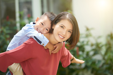 Young Asian woman giving piggyback ride to her little son
