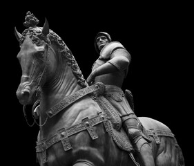 Sculpture of man on a horse isolated on black