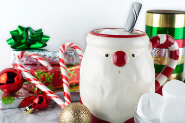 Santa Claus mug of hot cocoa with marshmallows, candy canes, presents, and ornaments on a white background.