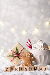 Cozy winter composition with a cup of hot chocolate with marshmallows gingerbread man cookies and gift on a light festive background. Christmas word from letters