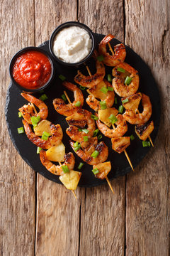 Fresh kebabs made from shrimps and pineapple slices decorated with green onions served with sauces close-up on a slate plate. Vertical top view
