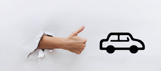 Hand with a raised thumb near the symbol of car. The concept of driving school, loan, mortgage, excellent quality automotive industry. Like, cool, good. Сlick like.