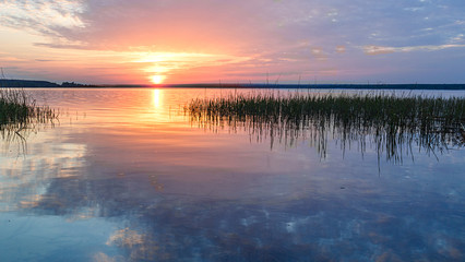 The rays of the dawn sun on the lake. Reflection of sunset clouds in the river. Rural landscape.