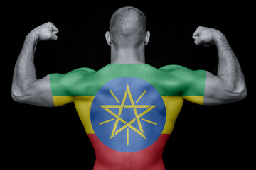 The back of a young athletic man wearing a T-shirt with the national flag of Ethiopia on a black isolated background. The concept of national pride and patriotism