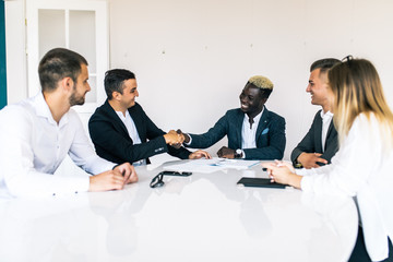 Business colleagues sitting at a table during a meeting with two male executives shaking hands. Team work