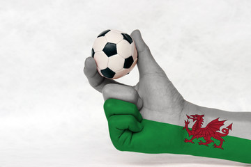 Mini ball of football in Wales flag painted hand, hold it with two finger on white background. Concept of sport or the game in handle or minor matter.