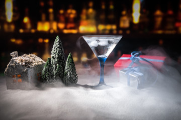 Winter Cocktail - Alcoholic drink and snow scene with a Christmas theme or Ideas and recipes for Christmas drink. Glass of martini on snow with Christmas decoration