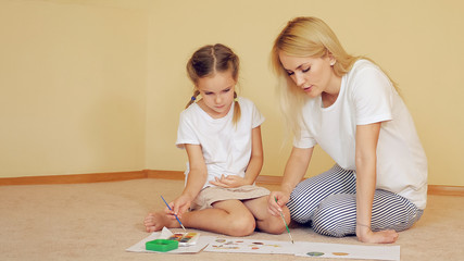 Beautiful woman with girl sitting on floor and drawing on paper with watercolor