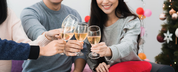 Young Asian man and beautiful woman drink champagne celebration with friend.Smiling face in room with Christmas tree decoration for holiday festival.Christmas Party and celebration banner background.