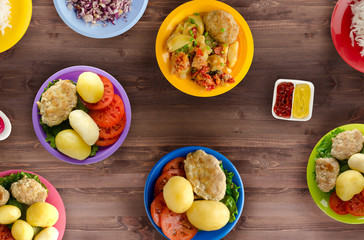 Tasty seasoned fried pork chops cooked in a spicy marinade are served with boiled potatoes, salads and sauces. Cutlets on a plate on a wooden table