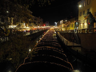 View of the crowded Naviglio Grande district in Milan and christmas lights.