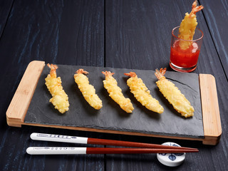 Shrimps tempura with sweet chili sauce on black slate board, set on a dark blue background