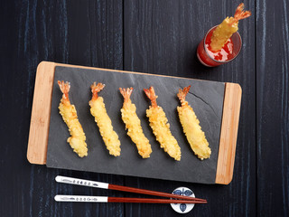 Shrimps tempura with sweet chili sauce on black slate board, set on a dark blue background, top view