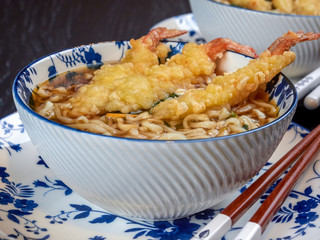 Closeup view of a bowl of tempura udong noodles, with shrimps temputa, in beige bowls with red chopsticks, on dark blue background
