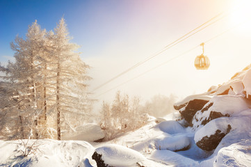 Cable car on the ski resort in winter mountains at sunset