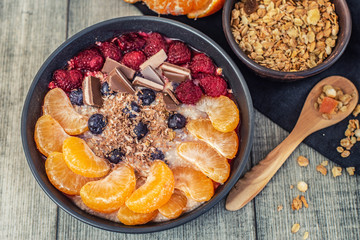 Oatmeal with tangerine, blueberries, chocolate and raspberry on grey background. Top view.