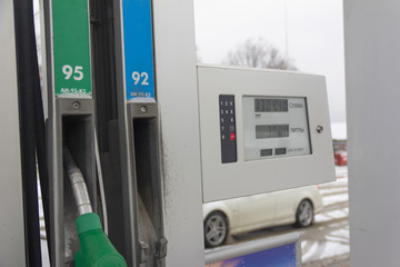 fuel dispensing gun and the name of gasoline brands in Russian AI 95 and AI 92, and an information panel in Russian with the words SUM, LITERS, PRICE PER LITER at a gas station in winter in Russia