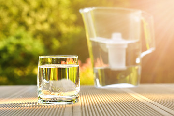 Clean glass of a clear water with a water filtration jug lit by sun rays in a green garden in warm summer day