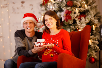 Photo of cheerful men in Santa cap with gift and pregnant woman