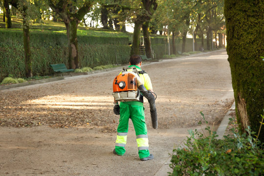 Gardener with blower backpack working in city park , blowing leafs. Autumn concept