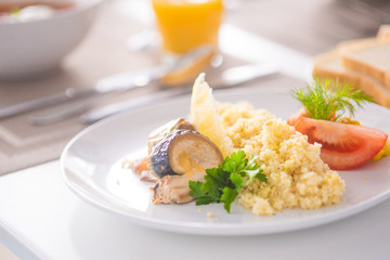 bulgur with vegetables and rolls of baked fish with corn, tomatoes and lemon on a white plate with orange juice