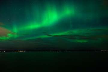 Green Aurora Borealis on night sky.