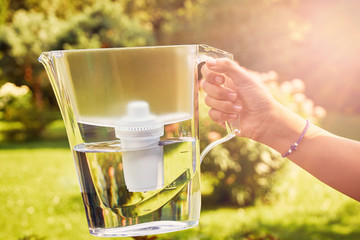 Girl's hand holds a water filter jug illuminated by sun rays in a sunny summer garden in a warm day
