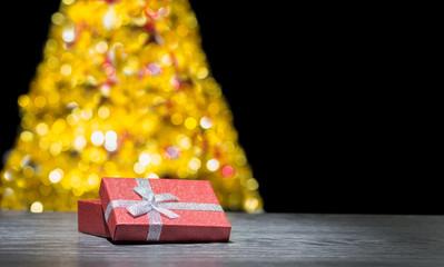 Fototapeta Prezent pod choinką. Prezent Bożonarodzeniowy. Tło świąteczne. Pudełko prezentowe na tle choinki. Miejsce na napis, życzenia.  obraz