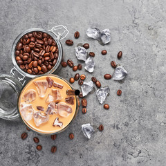 Cold brewed iced coffee in glass and coffee beans in glass jar on grey concrete background. Chocolate, vanilla, caramel or cinnamon iced coffee in tall glass. Top view, square crop.
