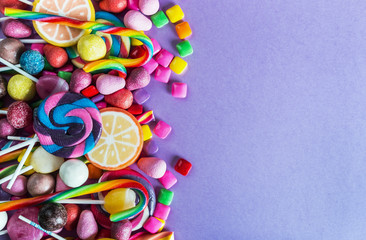 sweets, lollipop, chewing gum, candies etc on lilac background