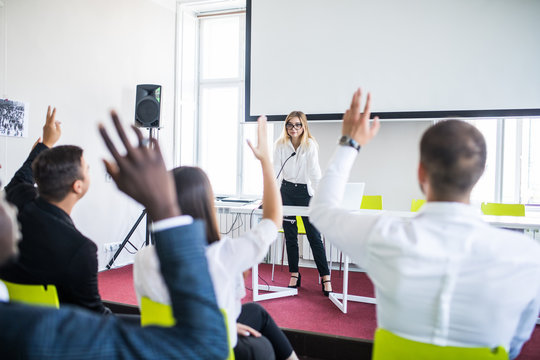 Business people Raising there Hand Up at a Conference to answer a question. Business conference.