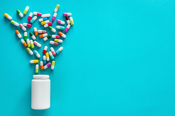 assortment of pharmaceutical medicine capsules, pills and tablets in bottle on blue background. Empty space for your text Wall mural
