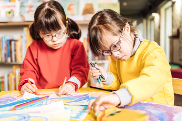 Sisters having Down syndrome feeling involved in coloring pictures