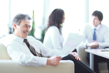 businessman pondering a document sitting in a modern office