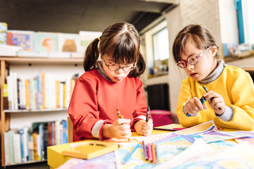 Funny sisters having Down syndrome holding crayons while drawing