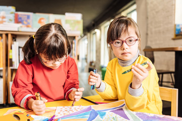 Dark-eyed sisters with Down syndrome coloring pictures together